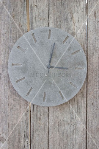 Hand-made concrete clock on board wall