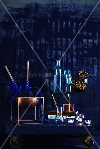 Blue and copper colour scheme - blue knitting in copper bowl and blue glassware on wooden board on castors