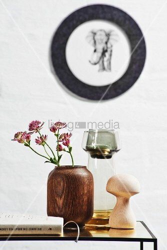 Wooden vase and toadstool ornament on side table below picture of elephant on wall