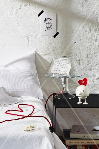 Bedroom decorated with love letter under clear lampshade and lamp power cable arranged as love-heart on bed