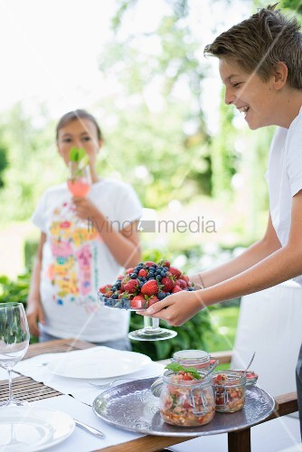 Laughing boy holding glass dish of fresh berries next to preserving jars on tray on garden table