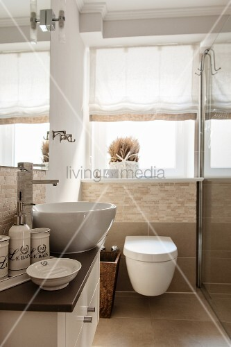Washstand with countertop basin, toiletries and toilet below window in small, modern bathroom