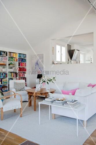 Moderner Wohnbereich mit filigranem Beistelltisch neben weißem Polstersofa und runder Holztisch, im Hintergrund in Wand fensterartige Öffnung