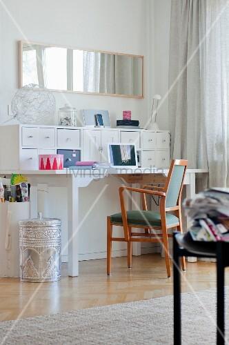 weiße Schubladenelemente auf Schreibtisch an Wand und Retro Armlehnstuhl, seitlich Papierkorb aus silberfarbenem Metall