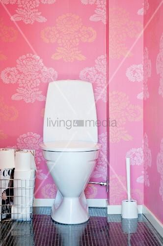 Toilette vor rosa Tapetenwand mit floralem Muster