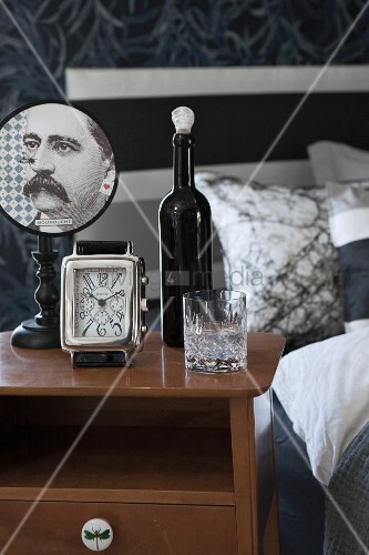 Bottle, glass, alarm clock and vintage table lamp with portrait of man on lampshade on bedside cabinet