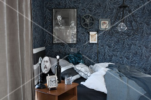 Bedside table and bed below poster of Charlie Chaplin and film reel on floral wallpaper
