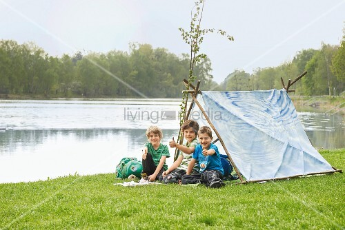 Children in tent made from branches and sheet on river bank