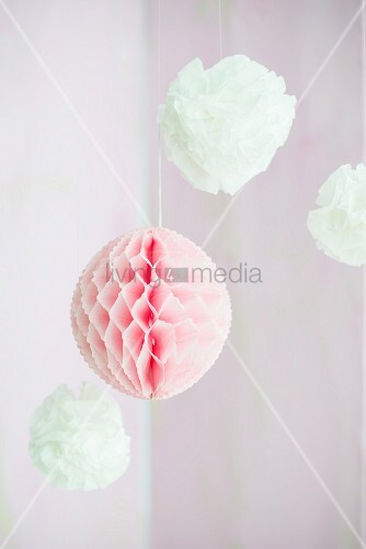 Pompoms and honeycomb paper ball suspended from ceiling