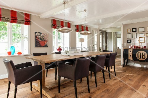 Brown leather chairs at long wooden table on rustic wooden floor
