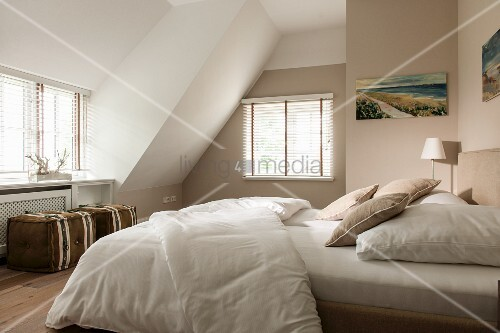 Beige bedroom with double bed and pouffes in converted attic