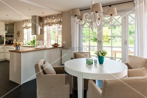 runder esstisch in weiss und helle polstersessel unter kronleuchter im hintergrund offene k che. Black Bedroom Furniture Sets. Home Design Ideas