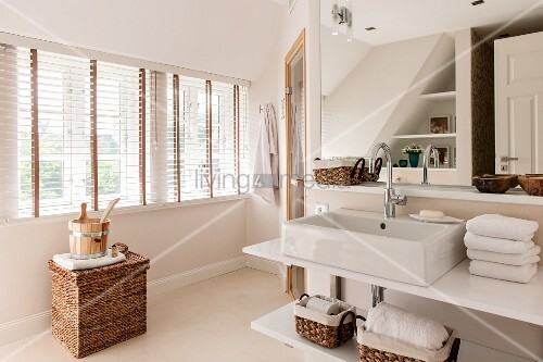Washstand with countertop sink and shelves; sauna bucket on top of wicker trunk below windows with louvre blinds