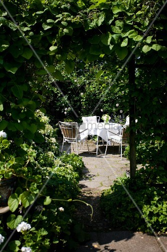 View of romantic seating area with table and chairs in summery arbour