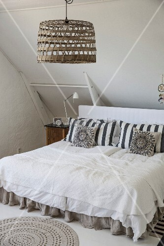 Double bed with pillows against headboard below pendant lamp with basketwork lampshade