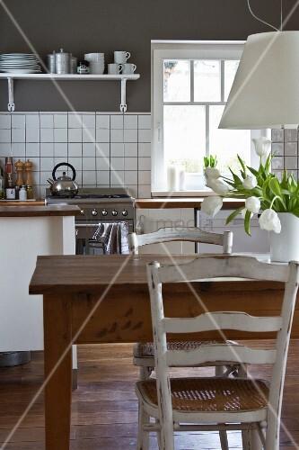 alter holztisch unter weisser h ngeleuchte in moderner k che mit weisser k chenzeile und grauer. Black Bedroom Furniture Sets. Home Design Ideas