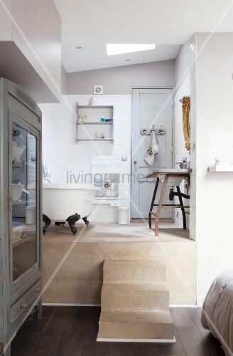Blick von Schlafzimmer in offenes Bad auf Podest mit Treppenstufen ...