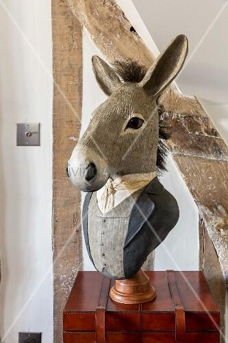 Kunstobjekt mit Eselkopf auf edlem Lederkoffer neben rustikalem Fachwerkbalken
