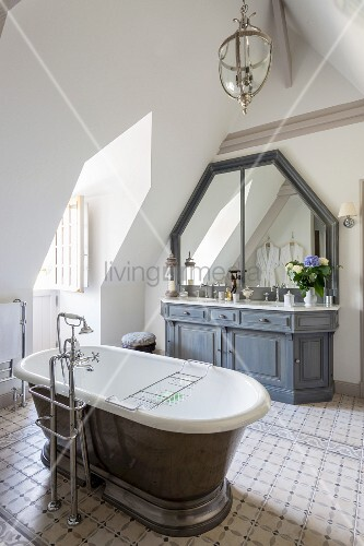 Free-standing vintage-style bathtub with floor-mounted taps on tiled floor and custom washstand with grey base cabinet in attic bathroom