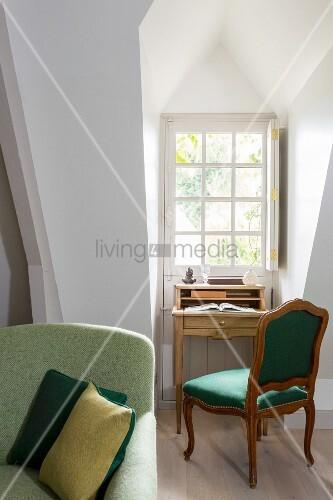 Schreibtischplatz mit antikem Polsterstuhl in Gaubennische vor Sprossenfenster
