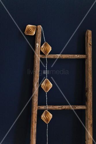 Alte Holzleiter mit Lichterkette an blauer Wand