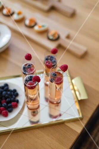 Aperitifs with berries on mirrored tray