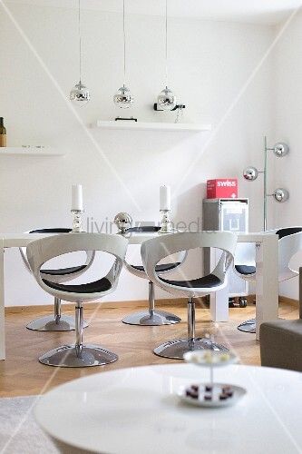 Glossy, white shell chairs in modern, white dining room