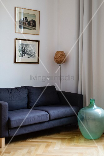 Green glass demijohn in front of blue sofa