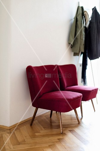 Red, retro easy chairs next to coat rack in hall