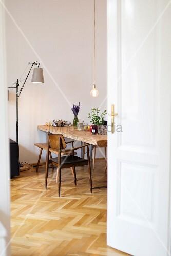 Blick ins Esszimmer mit Vintage-Stuhl und Fischgrätparkett