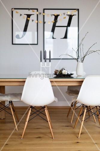 Schalenstühle am Esstisch, gerahmte Buchstaben an der Wand