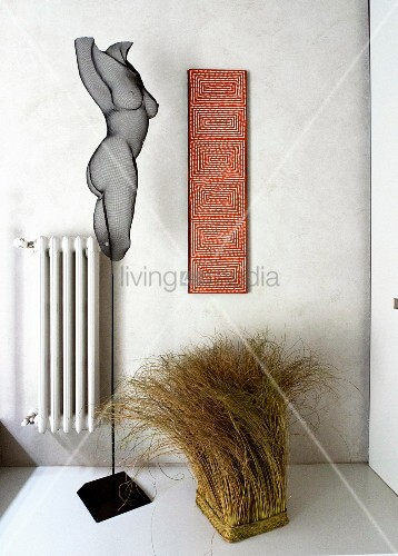 Metal sculpture and bundle of grass next to artwork and radiator on wall