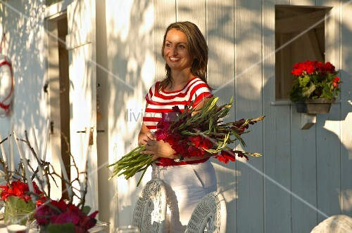 Cheerful woman holding red gladioli outside white wooden house