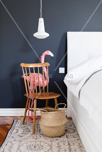 Flamingo behind Windsor chair used as bedside table against dark wall