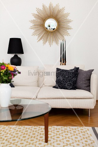 Glass coffee table in front of white sofa below sunburst mirror on wall