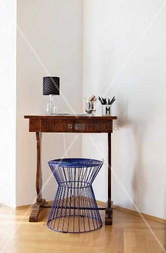 Blauer Drahthocker vor antikem Sekretär in Wohnzimmerecke, minimalistisches Flair