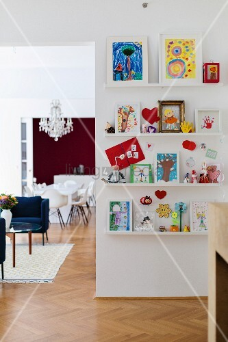 Colourful children's drawings on white floating shelves in open-plan interior
