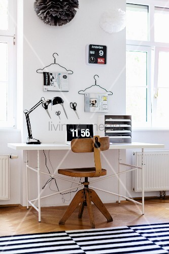 Vintage wooden swivel chair and white desk with classic metal frame below scissors and magazines on coathangers hung on wall