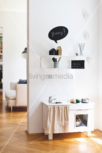 Weisse Kinderküche unter Wandboard in renovierter Altbauwohnung mit Fischgrätparkett