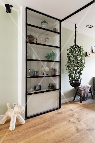 Metal door in front of shelving next to large macrame plant hanger