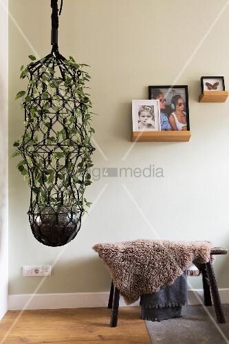 Blumenampel mit Makramee neben einem Hocker mit Schaffell
