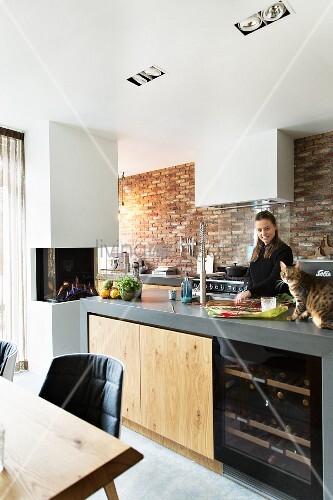 Frau und Katze in einer modernen Küche mit Backsteinwand