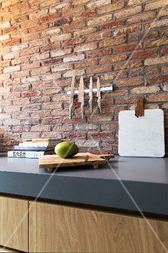 Magnetic knife rack on brick wall above grey kitchen worksurface