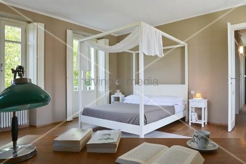 Elegantes Schlafzimmer mit weißem Bettgestell, Baldachin und dunklen Wänden