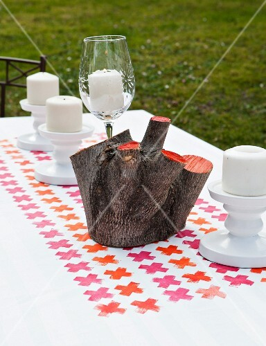 Painted wooden stump and candles on tablecloth printed with pink and orange crosses