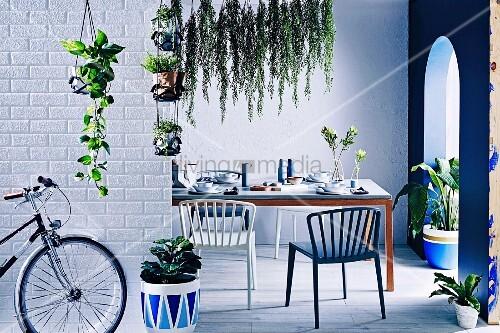Gedeckter Tisch in kühlem, blauem Ambiente mit Grünpflanzen und Rundbogendurchgang