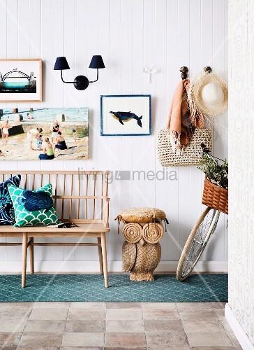 Hausflur mit Holzbank neben geschnitzter Eulenfigur als Hocker vor weisser Wandverkleidung mit Strandbild und maritimem Flair
