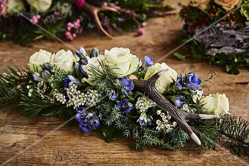Alpine-style arrangement of roses, gentian, antlers and conifer branches