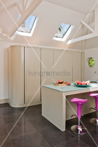 Modern kitchen with island counter, bar stools and kitchen counter behind sliding doors