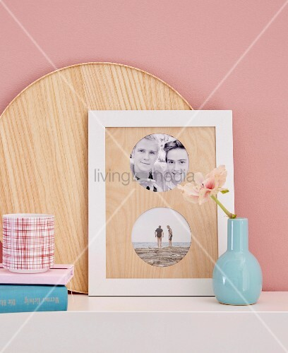 A blue vase next to framed photos with a homemade wooden passepartout